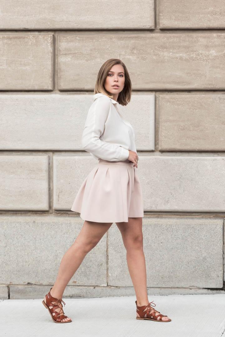 Photo de modèle sur la rue devant un mur de couleur et texture neutre et uniforme