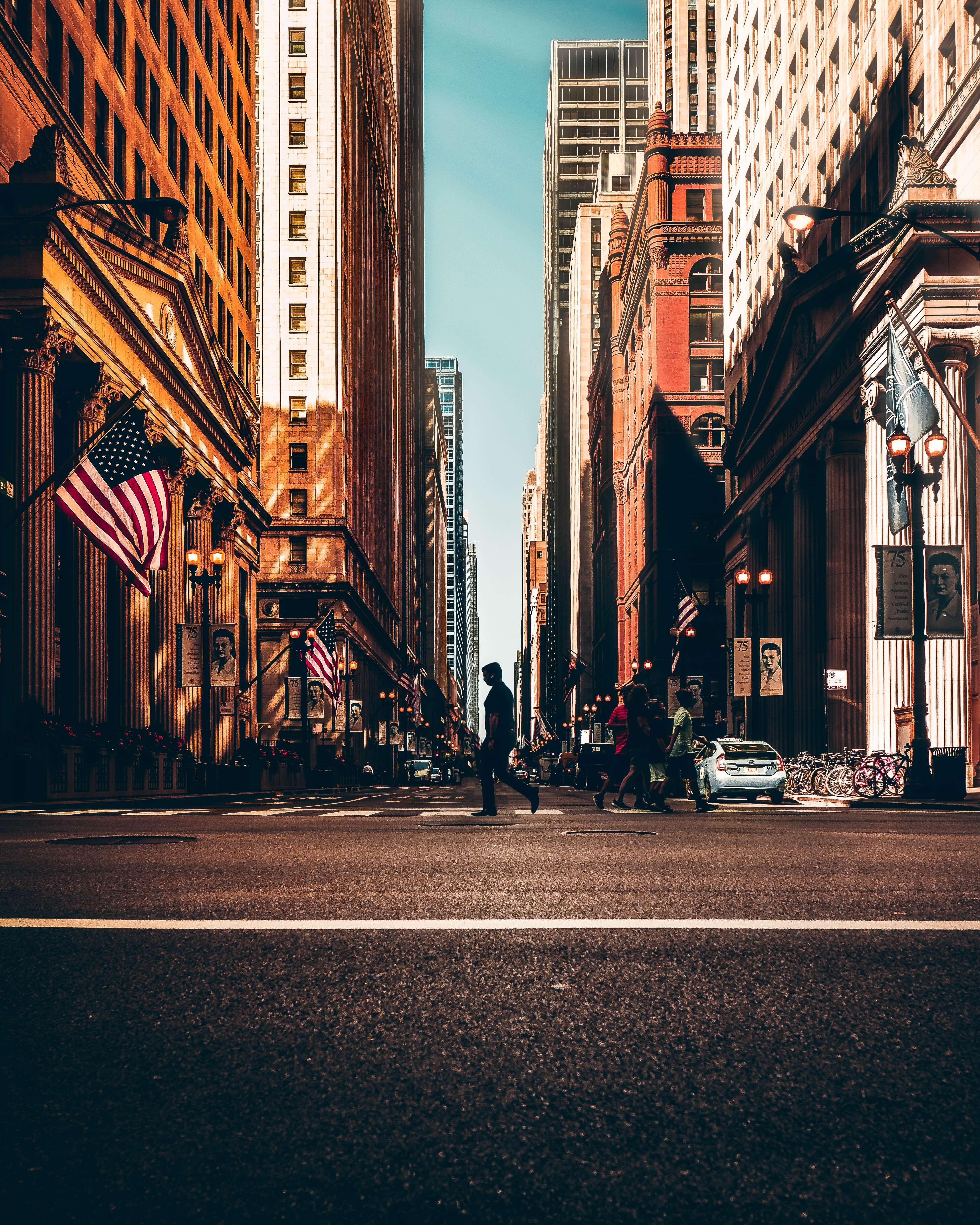 Piéton encadré par les édifices et les lignes au sol dans une grande ville américaine, par Benjamin Suter