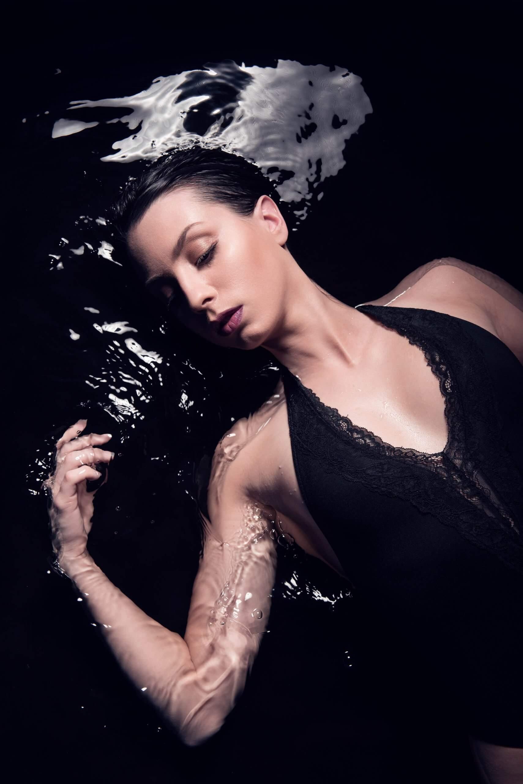 autoportrait dans une piscine d'eau noire avec une peau blanche cadavérique
