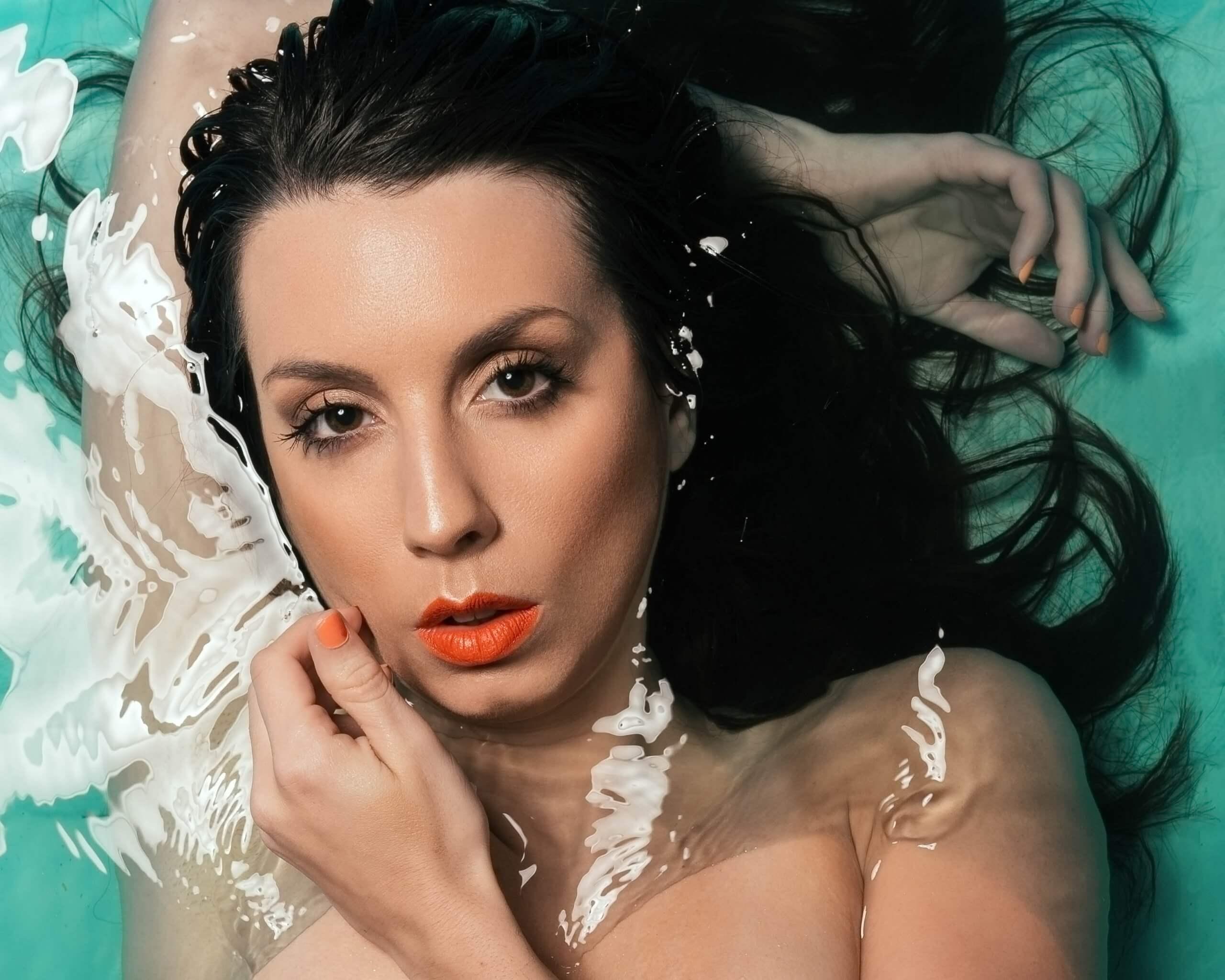 autoportrait dans le style d'un éditorial de mode, dans l'eau turquoise avec un maquillage orange