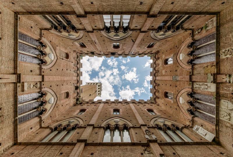 cour intérieure d'un bâtiment photographié en perspective à un seul point de fuite, symétrique de tous les côtés ou presque