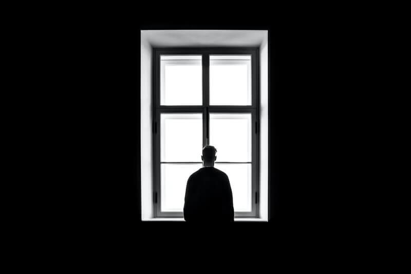Un garçon se tient debout au centre d'une fenêtre symétrique
